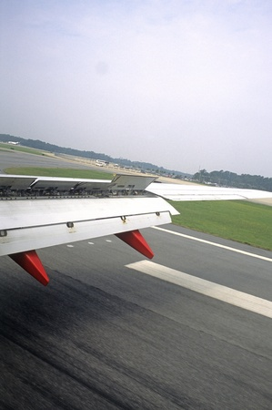 Airplane wing with flaps extended on take-off from small airport Orlando County Airport in Plymouth, Florida.