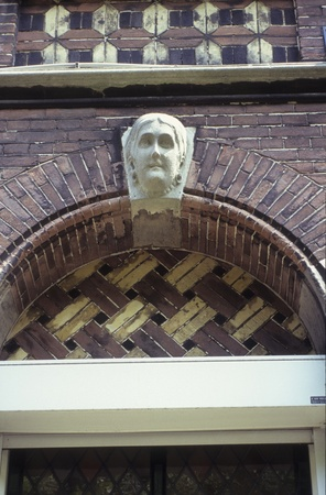Relief of the head of a woman at the peak of a window wells on a building in Haarlem, Netherlands. Rendering of fhair suggests that the model lived during the 1800