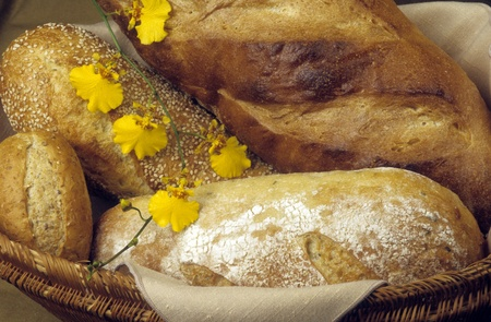 Basket of freshly baked loaves of bakery bread, decorated with yellow orchids.