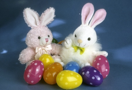 Two Easter bunny dolls, pinkwhite and whitepink, surrounded by brightly colored plastic eggs.