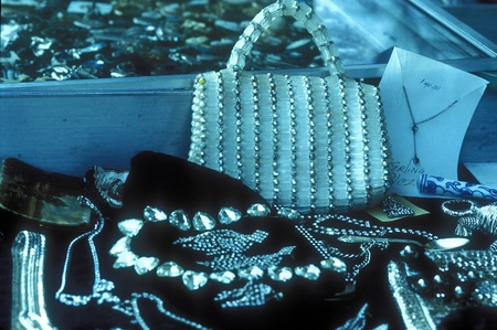 Collection of classy, vintage, costume jewelry and purse laid out on black background.