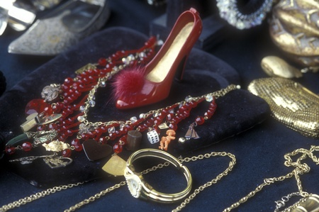 high heeled shoe: Vintage charm necklace and watch arranged around a high heeled shoe on a flea market sale table. Gold and red against blue background. Film scan.