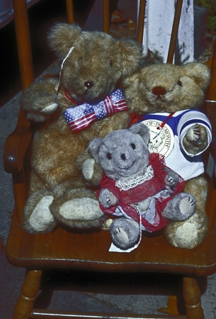 dora: Old teddy bears on wooden chair at Mt. Dora flea market in Florida.