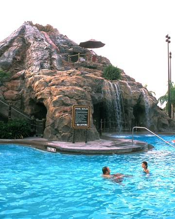 Waterfall on right with people swimming in pool at Disney