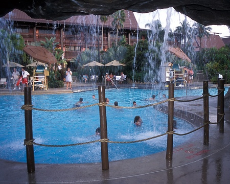 View from behind waterfall of people sitting poolside and swimming in pool at Disney Editöryel
