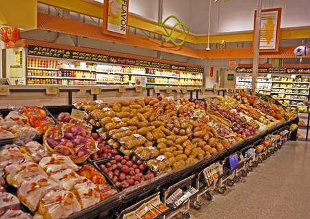 Oranges, red potatoes, white  potatoes, sweet potatoes, onions, pumpkins, squash, fruit juice, and more in a supermarket produce section.