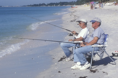 Two retirees fishing on the beach, sitting in lawn chairs at the water Editorial