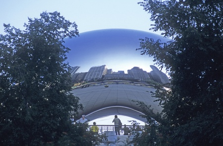 Cloud Gate reflects the tall buildings in Chicago, Illinois, as seen from Michigan Avenue.   Editorial