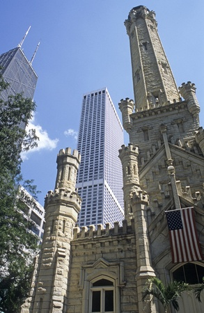 Chicago Water Tower building sits between tall buildings in downtown Chicago, Illinois, USA.