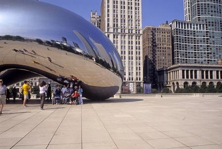 Tourists under the Cloud Gate in Millennium Park, Chicago, Illinois, USA, look at reflections in the Bean. Editorial