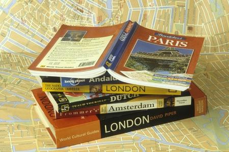 voyage: Guides de voyage empilés sur la carte
