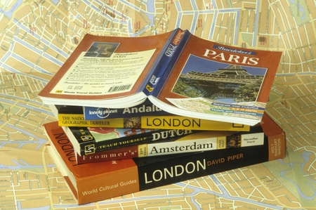 Travel guide books stacked on top of map