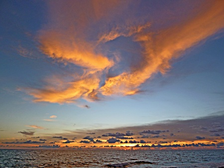 Beautiful red clouds snake across the sky in this sunset seen from Turtle Beach, Siesta Key, Sarasota, Florida, USA