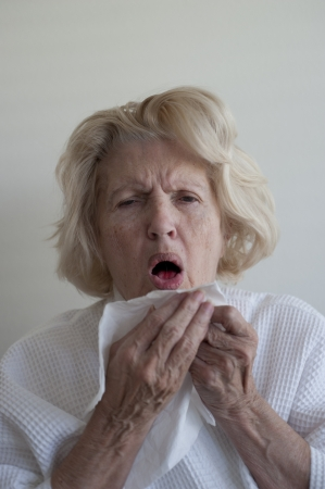 Blonde sick woman holds tissue and coughs.  Negative space at top is left for buyers copy.