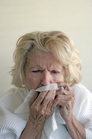 tosiendo: Mujer enferma con un virus del resfriado utiliza un pa�uelo de papel. Foto de archivo