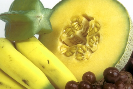 Group of healthy fruit including cut cantalope, bananas, grapes and cut starfruit