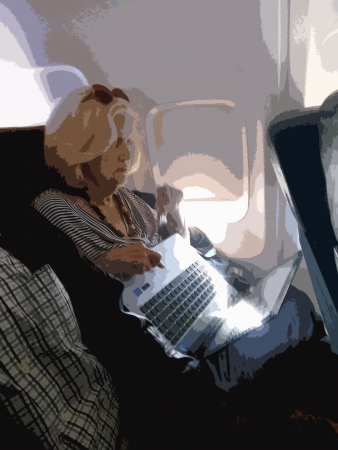 Woman uses a computer in cramped space on airplane