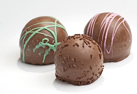 Three truffles, mint, strawberry, and raspberry flavored chocolate truffle candies.