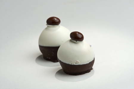 Two truffle candies with chocolate shell over soft chocolate centers. Imagens