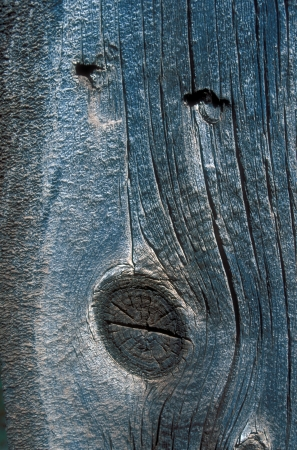 Weathered wood panel with two nails and knot that look like a face