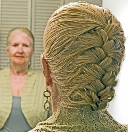 Blonde woman with French braids down the back of her head looks in a mirror