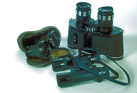 Two pair of binoculars and a pair of antique opera glasses in leather carrying case  Stock Photo