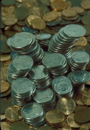 Stacks of American currency including copper pennies, silver nickels, quarters and dimes