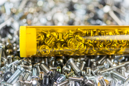 dismantle: Small screws in nice yellow box with bokeh background Stock Photo