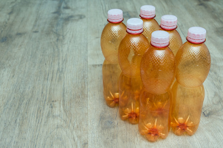 polycarbonate: Ecological separation of household waste. Empty plastic bottles in daylight on wooden floor. Stock Photo
