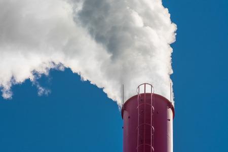 Dense white smoke ascending from red smokestack on blue sky