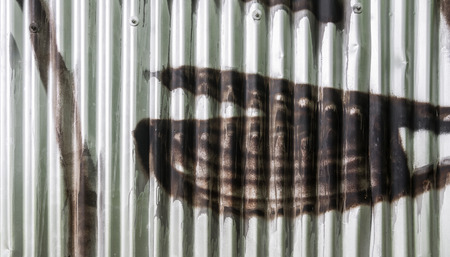 sidelight: Corrugated iron sprayed with brown color. Detail of graffiti on city fence. Stock Photo