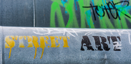 motto: Slogan street art on the steam pipe in a city. Creative graffiti.