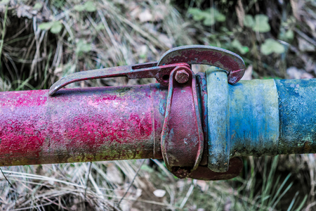 Coupling of red and blue pipe. Old color pipes with clutch. Fixed connection symbol. Stock Photo