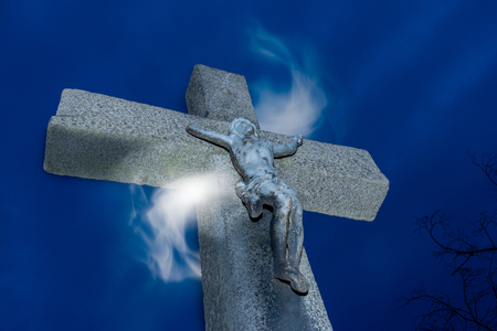 Crucifix with magical light. Jesus Christ on vintage stone cross under blue night sky with mystical haze. Concept of faith, hope, miracle, resurrection, canonization. Stock Photo