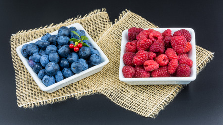 luscious: Raspberry and blueberry. Blue and red forest fruit in white bowls on a black background with decorative mat in HD ratio 16x9.