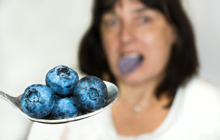stainless: Blue bilberry on stainless spoon. Fresh juicy berries and blurred woman in background. Stock Photo