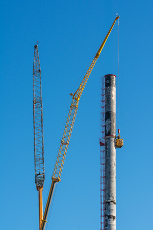 dismantle: Height work on scorched smokestack. Dismantling of chimney destroyed by fire using cranes. Stock Photo