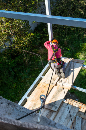 Safety of work at heights on construction. Protection a worker while working on building a balcony.
