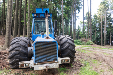 Harvester from the front in summer wood. Industrial background with the logging machine next to a forest path.