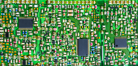 Impressive printed circuit board with many electronic parts. Varied electrotechnical background with surface mount of components in green shade. Banque d'images