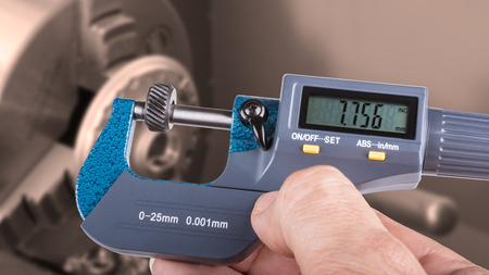 Detail of human hand with digital micrometer. Accurate measurement of knurling tool with a lathe in the background.