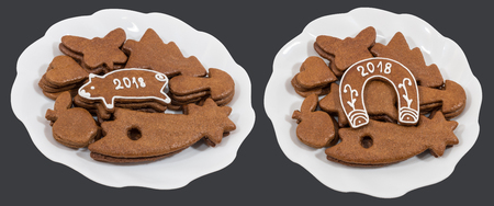 Two white plates with Christmas and New Year gingerbreads. Piggy and horseshoe for good luck with 2018 inscriptions. Isolated on a dark gray background.