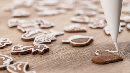 Close-up of decorating a christmas gingerbread in heart shape. Painting of pastry using icing bag with sugar frosting on wood table. Small depth of sharpness.