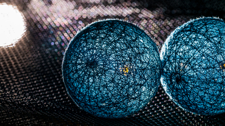 Detail of two spheres from black fibers with mystery light. Touch of blue balls with bokeh on background. Idea for science fiction, fantasy, technology or industry. Stock Photo