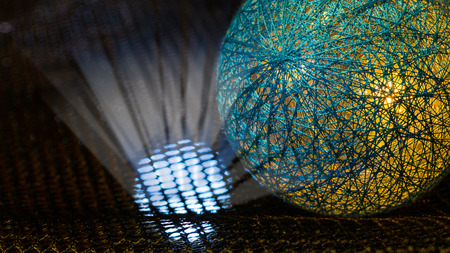 Detail of a sphere covered by net from fibers and mystery light rays in black space. Abstract background. Idea of danger, nuclear weapons, radiation, technology or sci-fi.