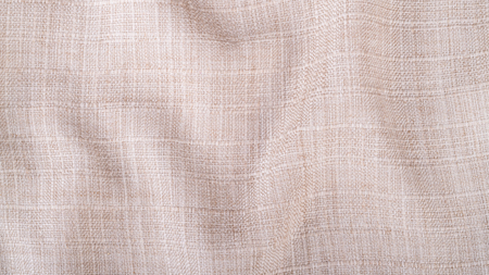 Decorative texture from wavy fabric. Stylish beige background from creased textile with copy space. Stockfoto