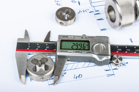 Measurement of thread cutting die by calipers and technical drawing. Metal engineering parts and the digital measuring tool placed on the manufacturing documentation. Stock Photo
