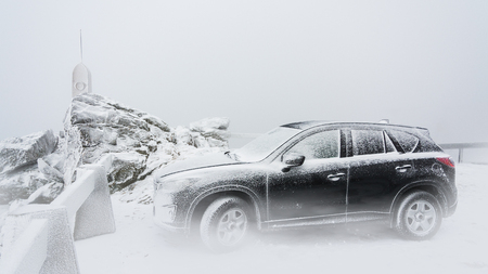 Black family car on a snowy mountain peak. Frosty wintry scene with the sport utility vehicle standing inside a cloud on the mountain top.
