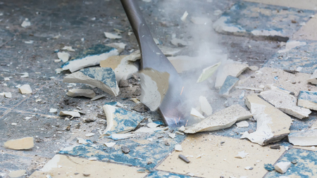 Removal of old floor during a renovation of housing. Idea of manual work. Close-up of a chisel from demolition hammer, fragments of ceramic tiles, dust and small sparks.