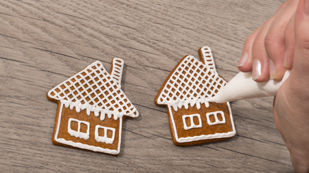 Close-up of a female hand while decorating sweet gingerbreads on a wood table. The woman is painting the house on the biscuit using a icing bag with sugar frosting. Standard-Bild